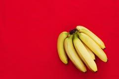 Bunch of bananas on red   background. Fresh organic Banana, Fresh bananas on kitchen table Royalty Free Stock Images
