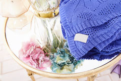 Bunch of beautiful lush fragrant hydrangea flowers stand in transparent glass vase gold plaid blanket knit from wool acrylic silk Royalty Free Stock Photo