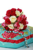 Bunch of beautiful roses on a pillow. A bunch of red and white roses lays on a turquoise pillow Stock Photography