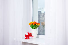 Bunch of beautiful tulips and gift box on a window sill Stock Photo