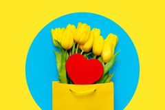 Bunch of beautiful yellow tulips in cool shopping bag. And heart shaped toy on the wonderful blue background stock images
