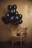 Bunch of black balloons and chair on gold background Stock Image