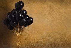 Bunch of black balloons on gold background. Stock photo Royalty Free Stock Images