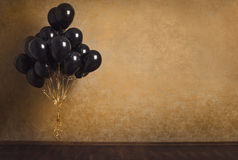 Bunch of black balloons on gold background Stock Photography