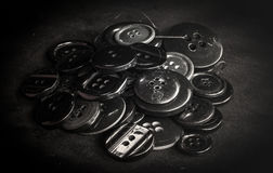 A bunch of black buttons. On a black velvet Royalty Free Stock Image