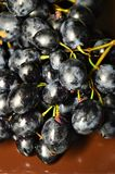 Bunch of black grapes on a brown plate royalty free stock photo
