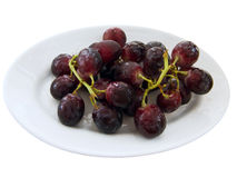 Bunch of black grapes on a white dish. Royalty Free Stock Photos