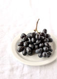 Bunch of black grapes on a white plate Royalty Free Stock Image