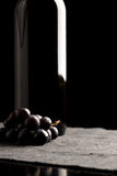 Bunch of black grapes with a wine bottle Royalty Free Stock Photography
