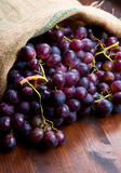 Bunch black grapes on wooden background Royalty Free Stock Photo