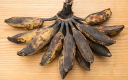 Bunch of black overripe bananas on wooden background Stock Photo