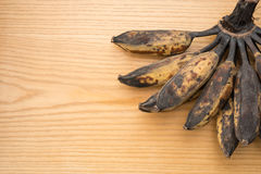 Bunch of black overripe bananas on a wooden background Stock Photos