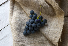 Bunch of blue grapes on wooden background Royalty Free Stock Photo