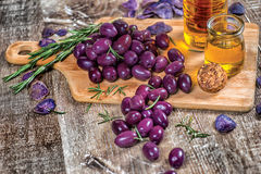 Bunch of blue olives on the table on a wooden board. Olives are Stock Photo