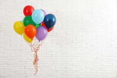 Bunch of bright balloons near wall, space for text. Celebration time. Bunch of bright balloons near brick wall, space for text. Celebration time royalty free stock photos