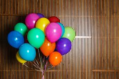 Bunch of bright balloons on wooden background royalty free stock image