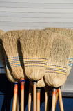 Bunch of brooms. Bunch of straw brooms leaning on a wall Stock Photo