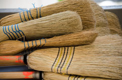 Bunch of brooms. Bunch of straw brooms lying on floor Royalty Free Stock Photos