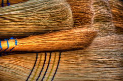 Bunch of brooms. Bunch of straw brooms lying on top of each other Stock Photos