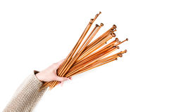 Bunch of brown bamboo wooden knitting needles in woman hand on white background. Top view Royalty Free Stock Images