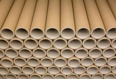 A bunch of brown industrial paper core. A lot of paper cores or paper tubes. Brown paper rolls stock image
