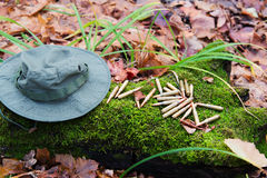 Bunch of bullets lying on the moss. Beside hat Royalty Free Stock Photography