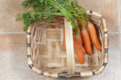 Bunch of carrots on a basket, on a tile background Stock Photography