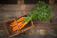 Bunch of carrots in basket, wood Royalty Free Stock Photo