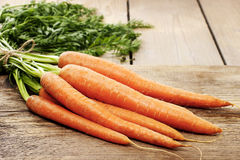 Bunch of carrots on wooden table Stock Photo