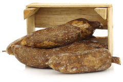 Bunch of cassava roots in a wooden crate stock images