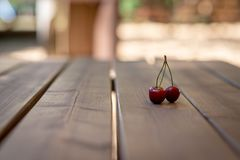 A bunch of cherries on a wooden table surface. A bunch of cherries on a wooden table surface royalty free stock photos