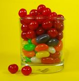 A glass full of colorful candies with a yellow background Royalty Free Stock Image