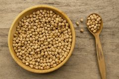 Bunch of chickpeas in a bowl and spoon on old wooden background Stock Photos