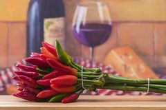 A bunch of chili peppers. With wine and cheese Royalty Free Stock Photography