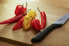 Bunch of chilies on a cutting board. Knife next to Stock Photo