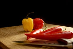 Bunch of chilies on a cutting board. Seen from the side Stock Photos