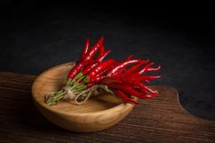 Bunch of chilli peppers in wooden bowl on cutting board on dark background royalty free stock photography