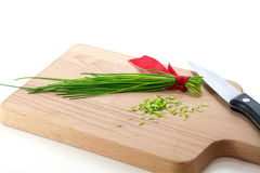 Bunch of chives and kitchen knife on a cutting board Royalty Free Stock Image