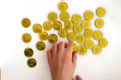 Bunch of chocolate gold coins with the hand of man on white background stock photography