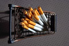 A bunch of cigarettes lying in a metal mini cart. Bad habit. The dependence on nicotine stock photography