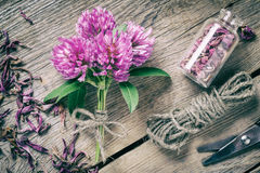 Bunch of clover, bottle with dried herb and jute rope Stock Image