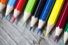 Bunch of color pencils. Over a wooden background Stock Photos