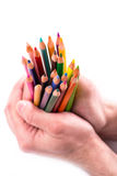 Bunch of color pencils in hands Royalty Free Stock Image