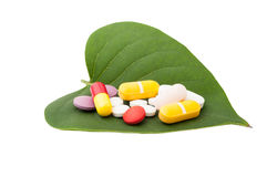 Bunch of colored pills on a green leaf Stock Images