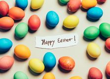 Bunch of colorful eggs and. `Happy Easter` card in the middle. Holiday wishes Stock Photos