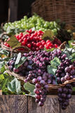 Bunch of Colorful Grapes in Wicker Basket on Wooden Shelf Royalty Free Stock Images
