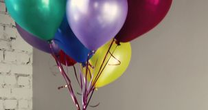 Bunch of colorful helium balloons soar up indoors