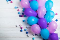 Bunch of colorful party balloons with paper stars on white wooden background stock images