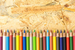Bunch of colorful pencils, on flakeboard surface Royalty Free Stock Images