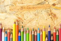 Bunch of colorful pencils, on flakeboard surface Royalty Free Stock Photography